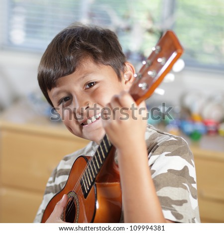 A young smiling boy plays his guitar or ukulele - stock photo