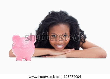 A young smiling girl is resting her head on her hands with a piggy bank in front of her against a white background