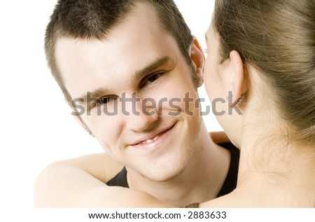 A young smiling man hugging his girlfriend on white background