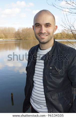 A young smiling man is standing by a lake