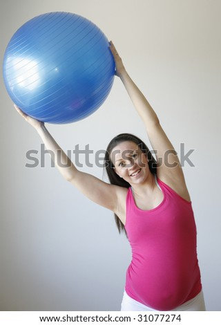 A young smiling pregnant woman in a pink shirt exercising and stretching using a blue fitness ball while standing up. - stock photo