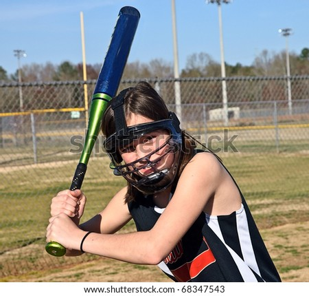 A young softball player with safety equipment on ready to hit the ball. - stock photo