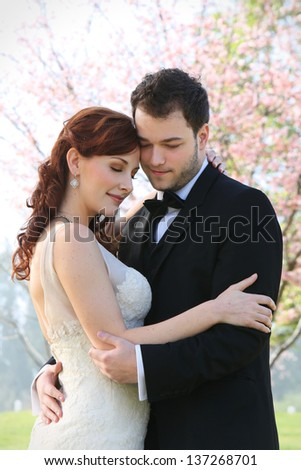 A young 20 something bride and groom hold each other in a loving embrace. Photograph features a cherry blossom background