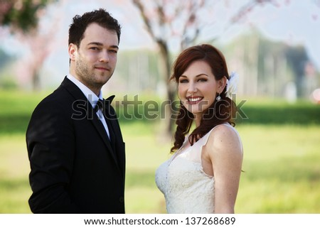 A young, 20 something, man dressed in a black suit with a bow tie and woman in a sleeveless white wedding gown stand in  a grass meadow with cherry blossom trees in the background. - stock photo