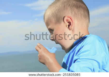 A young sport boy using inhaler outside - stock photo