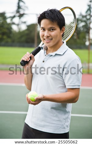 A young sporty asian male playing tennis