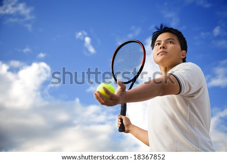 A young sporty Asian male playing tennis outdoor - stock photo