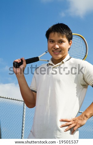 A young sporty asian man playing tennis - stock photo