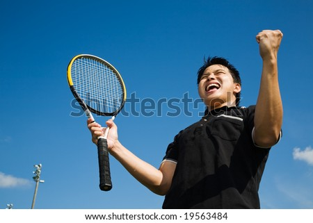 A young sporty asian tennis player screaming in joy of victory - stock photo