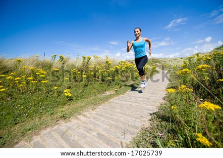 A young sporty woman running in the countryside - stock photo