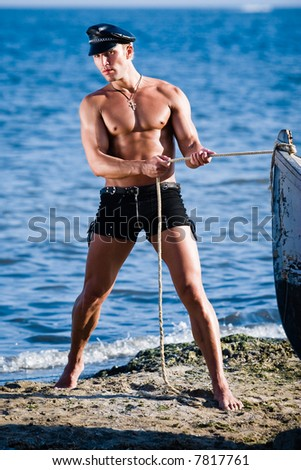 a young stripper posing on the beach as a sailor - stock photo