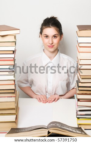 A young student sitting beside a pile of books