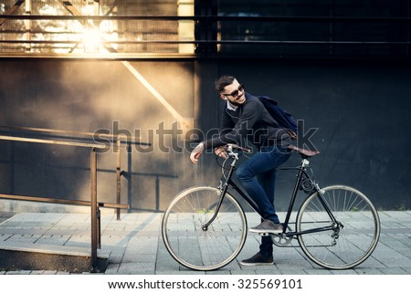 A young stylish businessman going to work by bike.  - stock photo