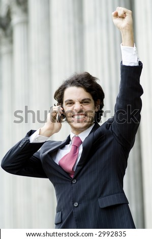 A young successful businessman celebrates whilst holding mobile phone