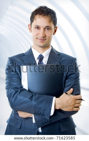 A young, successful handsome business man with pen and notebook smiling at office building in a light and modern business hall. - stock photo