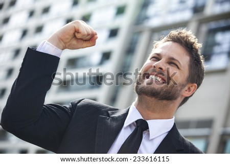 A young successful man, male executive businessman arms raised celebrating cheering shouting in front of a high rise office block in a modern city - stock photo