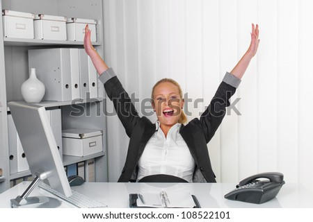 a young successful woman sitting at her desk in the office. - stock photo