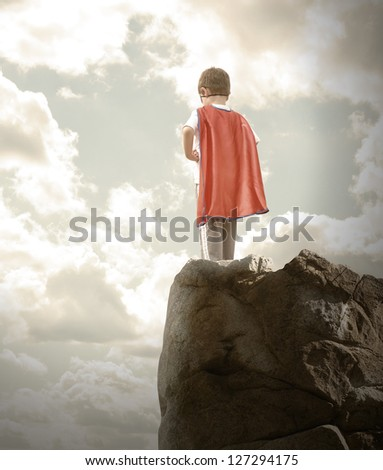 A young super hero boy is wearing a red cape and standing on a rocky cliff looking at a cloudy sky with copyspace. - stock photo