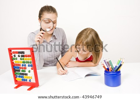 A young teacher checking her student 's actions, watching over her work with a magnifying glass - against white wall. - stock photo