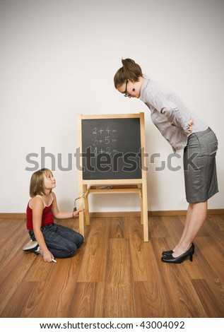 A young teacher looking strait at her student, the little girl bound to the blackboard with a handcuff - abstract illustration of strict teaching. - stock photo
