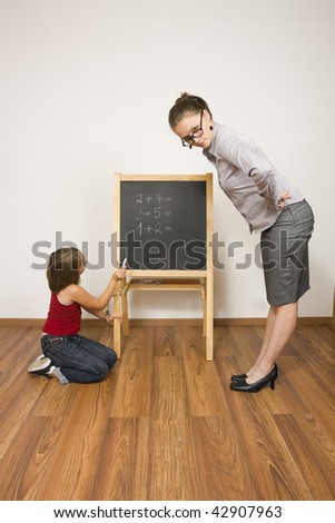 A young teacher looking strait atthe camera, the little girl fetterred to the blackboard with a handcuff - abstract illustration of strict teaching. - stock photo