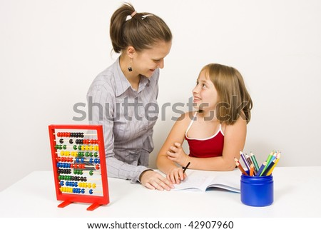 A young teacher, or mother, and her student, or little daughter, smiling to eachother, studying together against white wall - some educational tools and objects on the table. - stock photo
