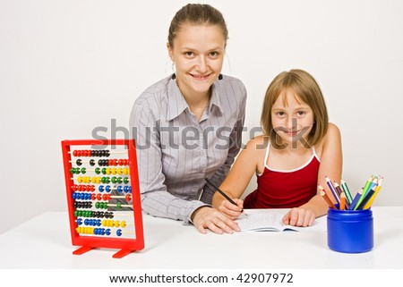 A young teacher, or mother, smiling to the camera together with a little girl against white wall - educational tools and objects on the table. - stock photo