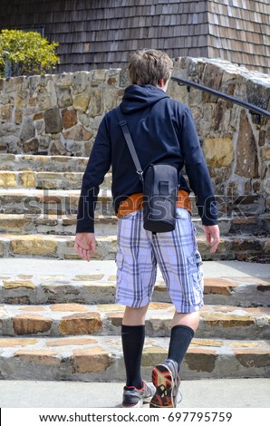 A young teen boy hiking up the stairs to the top of Brasstown Tower overlook in north Georgia.  He is carrying a camera lens.