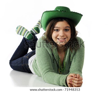 A young teen girl on the floor waiting for St. Patrick's Day celebrations.  Isolated on white.