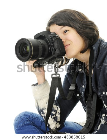 A young teen girl sitting in the corner of the image, happily taking pictures with a pro camera.  On a white background. - stock photo