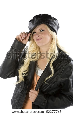 A young teenage girl in a black jacket and hat.  She has a smirk on her face.