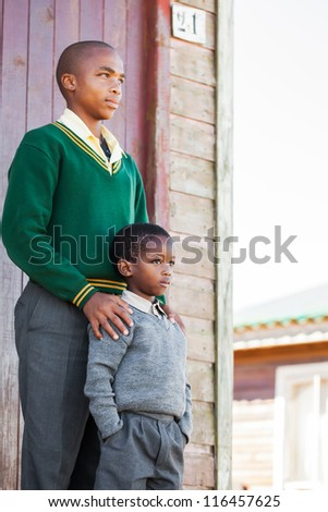 A young teenager and his little brother. - stock photo