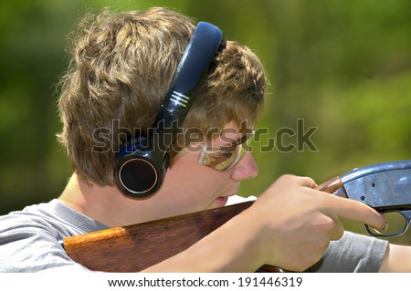 A young teenager learning to shoot targets with a shotgun. - stock photo