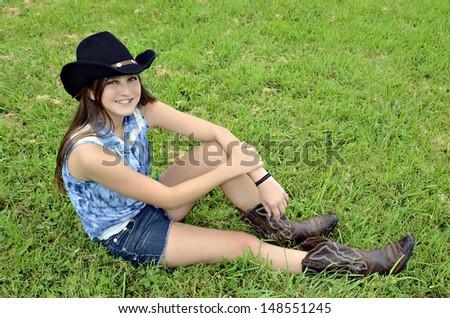 A young teenager with western hat and boots sitting in the grass smiling. - stock photo