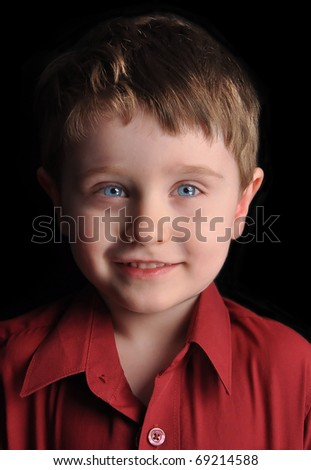 A young three year old boy is against a black background with blue eyes and smiling. - stock photo
