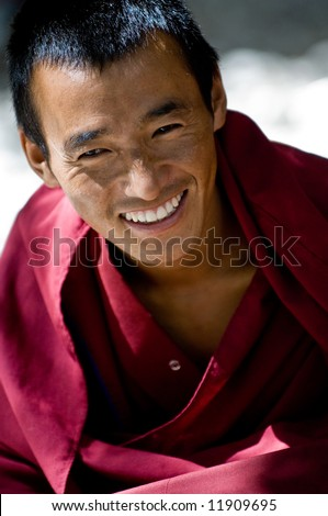 A young tibetan monk in burgundy robes smiling - stock photo
