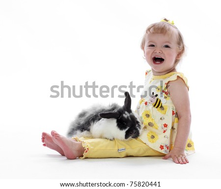A Young Toddler Girl Plays With a Bunny - stock photo