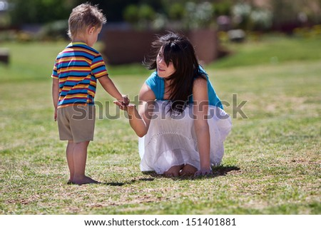 A young toddler giving something to he's beautiful mother while they are on the grass in summer.