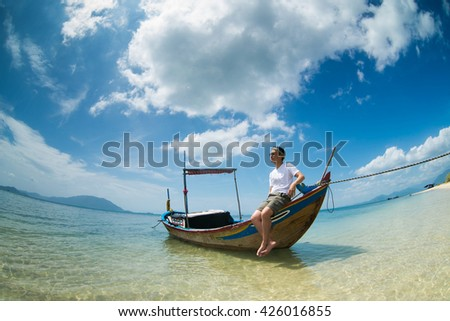 A young tourist on boat in Diep Son beach, Nha Trang, Vietnam.