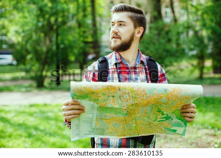 A young tourist with a beard holding a map and looking to the side, in the park - stock photo