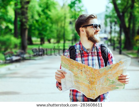 A young tourist with a beard laughing, holding a map and looking to the side in the alley in the park - stock photo