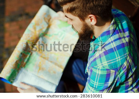 A young tourist with a beard sitting and looks at the city map, close-up - stock photo