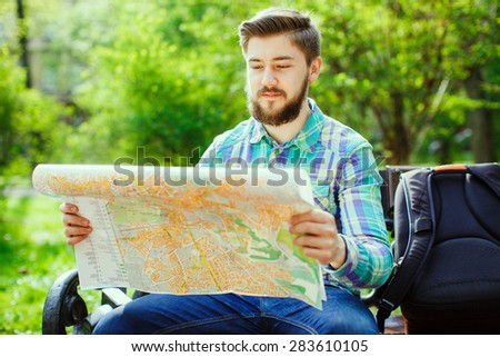 A young tourist with a beard sitting on a bench in the park, and looks at the city map - stock photo