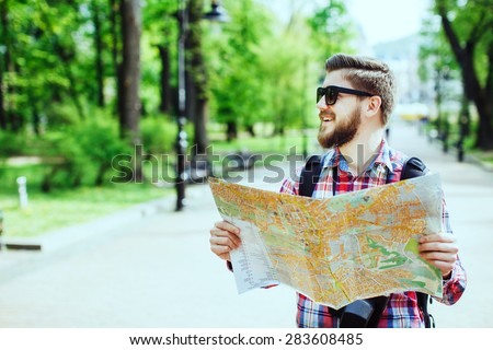 A young tourist with a beard smiling, holding a map and looking to the side in the alley in the park, profile - stock photo