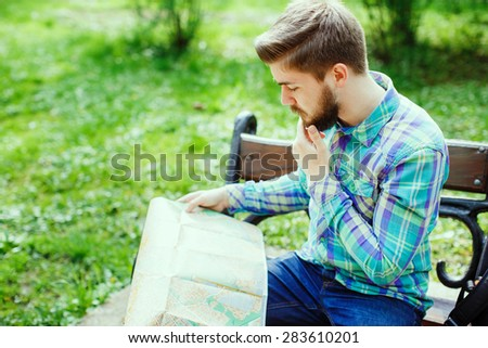 A young tourist with a beard thinking and looking at a map, sitting on a bench in the park - stock photo