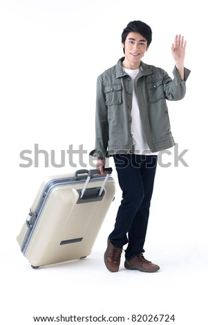 A young traveler man waving hand and pulling his luggage, come back from taken vacation - stock photo