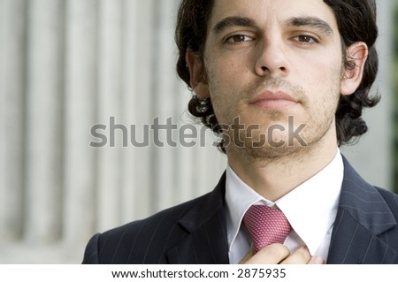 A young trendy businessman holding his tie