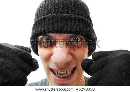 A young troubled bandit criminal robber thief with a black beanie and black gloves, isolated on white background, holding his fists up to the camera. - stock photo