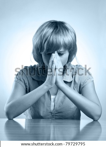 A young upset woman sitting at the desk - stock photo