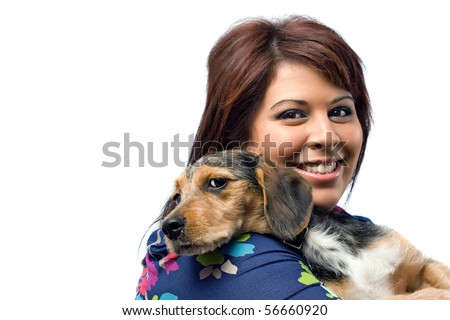 A young veterinarian holding a cute mixed breed beagle yorkie ( borkie ) dog isolated on a white background with copy space. - stock photo